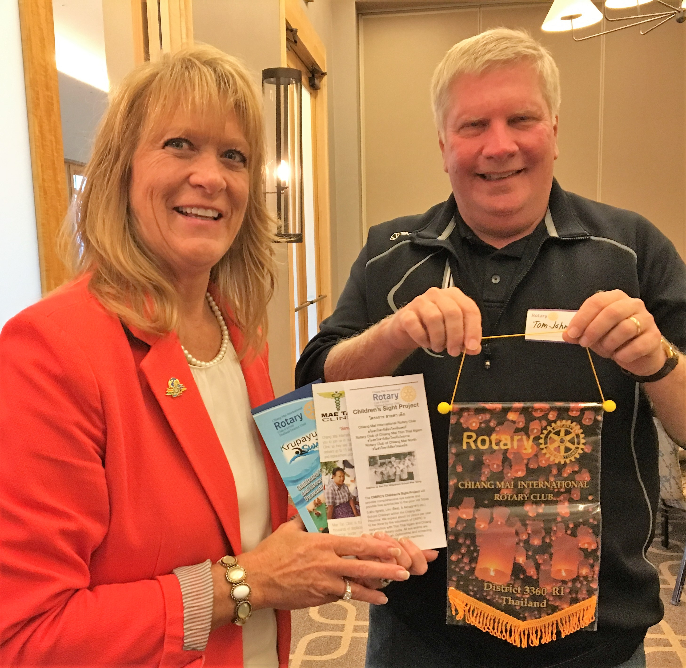 Tom Johnson presents President Char Weber with a flag from the Rotary Club in Chiang Mai, Thailand